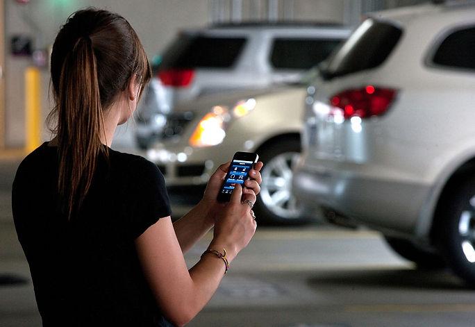 Mulher no celular em estacionamento