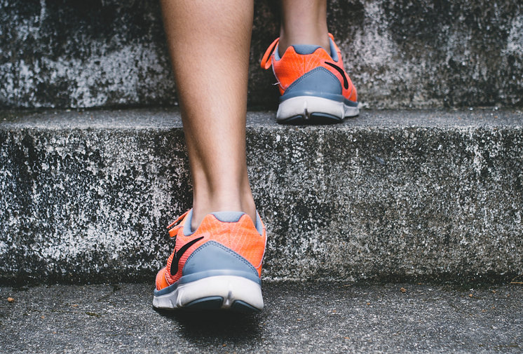 person wearing orange and gray Nike shoe