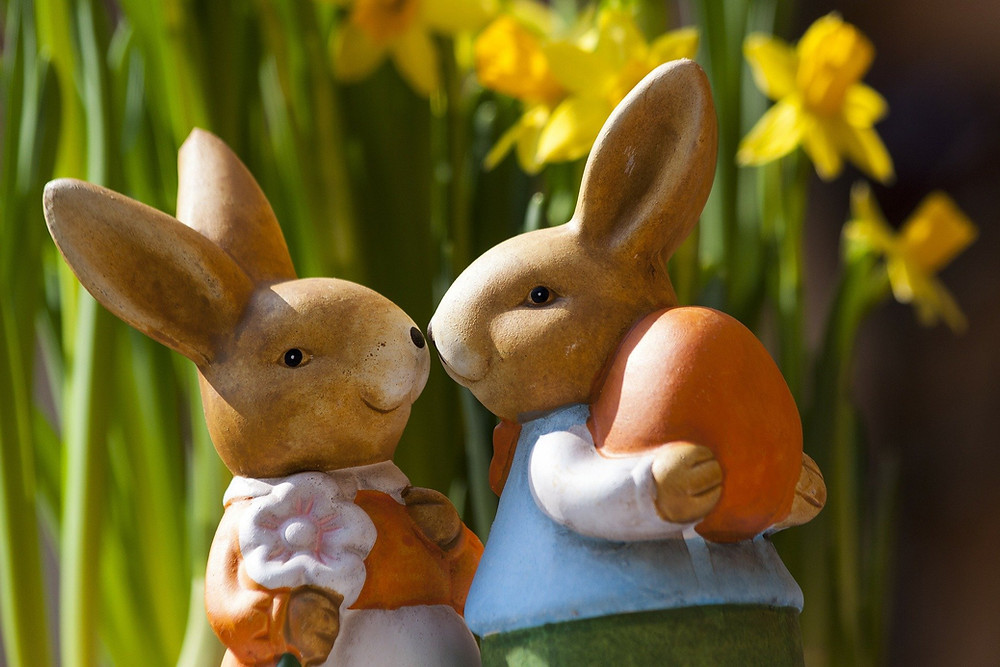 Two bunnies - one holding a flower and the other holding an Easter egg