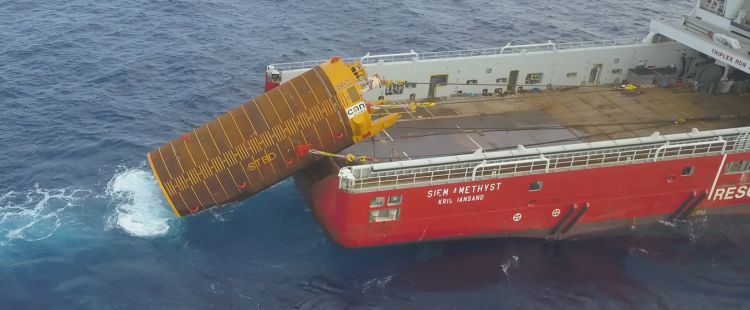 The CAN-ductor is seen being deployed from a vessel, partially submerged in the ocean.