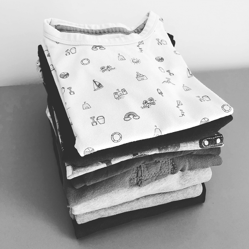 Black and white photo of a folded pile of kids clothes. The top item is a tshirt with rainbows and sea side icons.