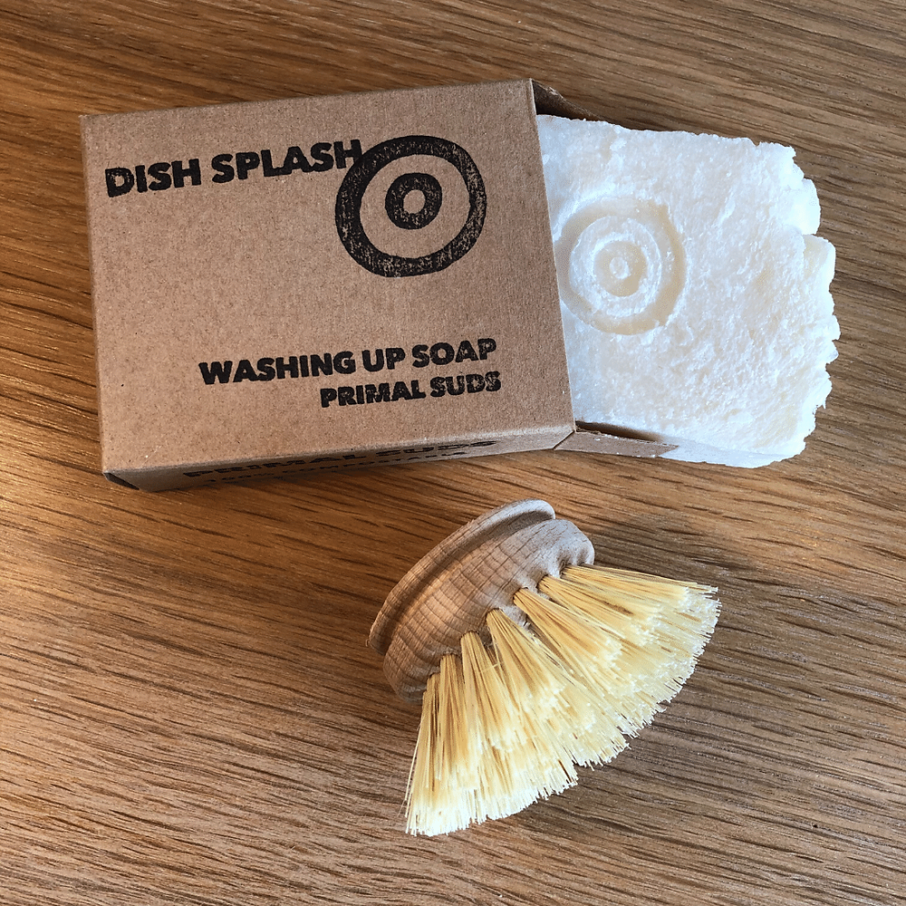 A soap bar with cardboard box is shown next to a wooden scrubbing brush