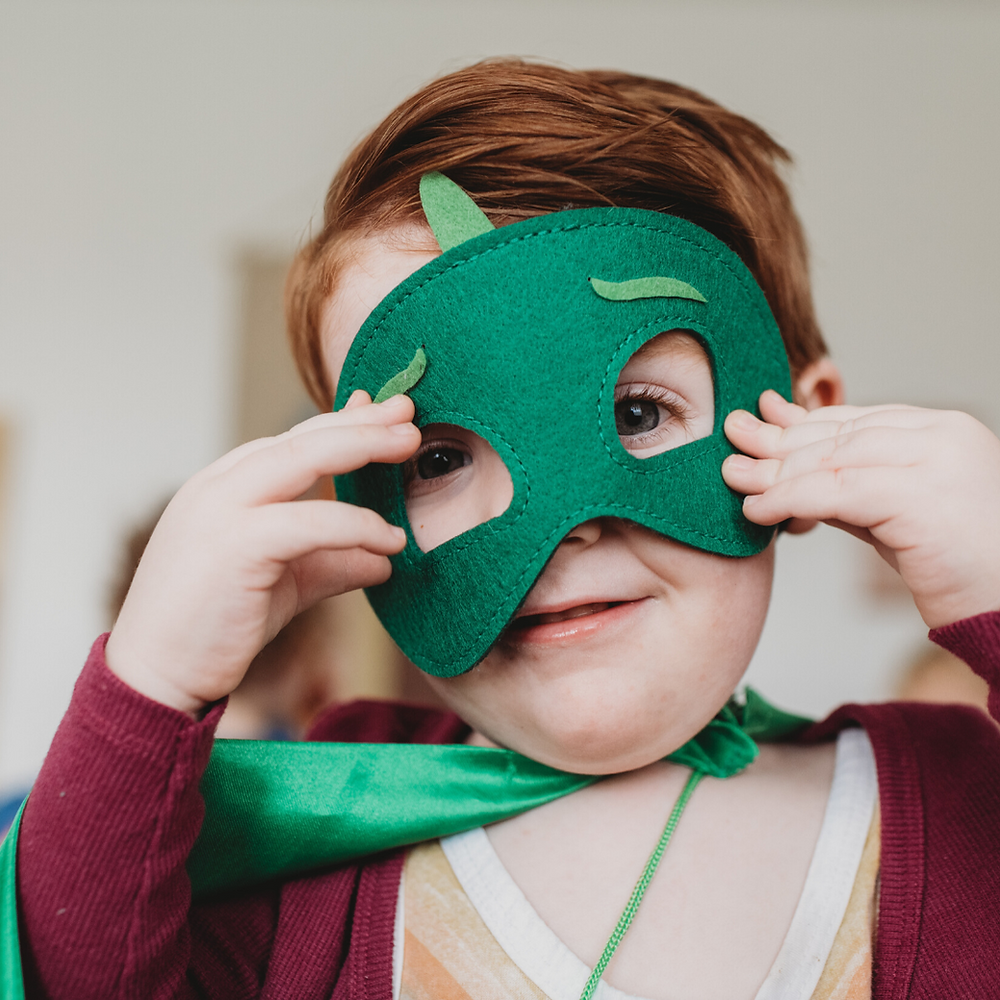 Young child smiles wearing a green superhero mask and cape