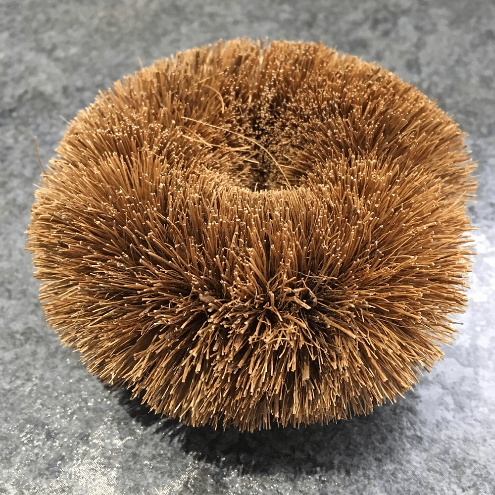 Round pan scourer which looks like a donut made from coconut husk