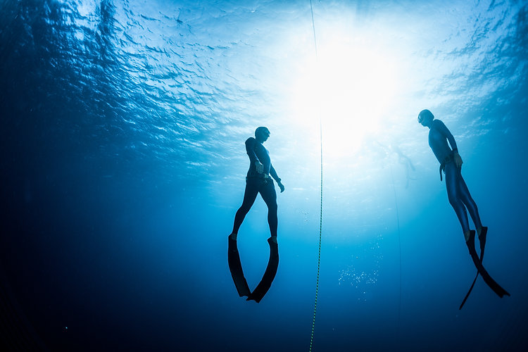 Two free divers, man and woman, ascendin