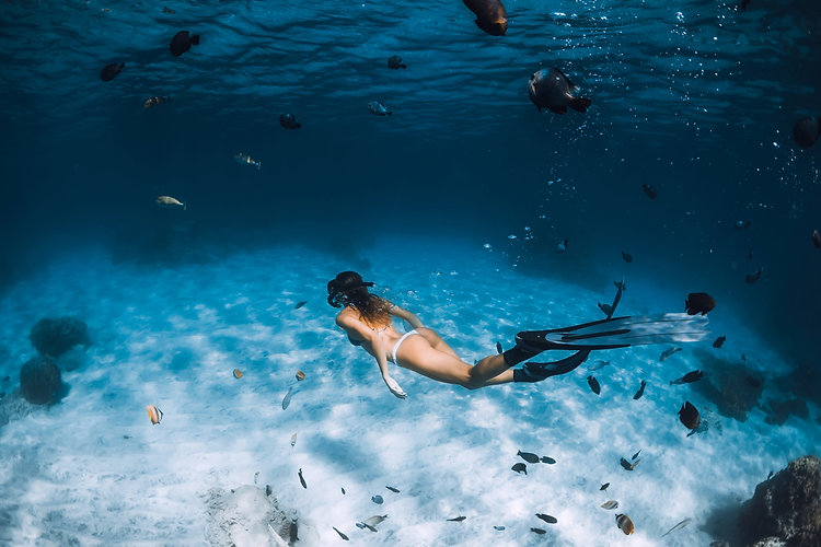 Freediver girl with fins glides over san