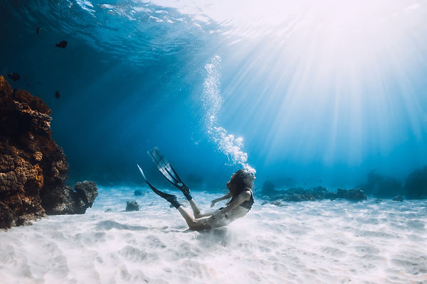 Young woman freediver make bubbles in de