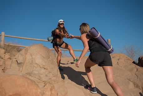 Image of girl helping another person on a guided hiking tour.