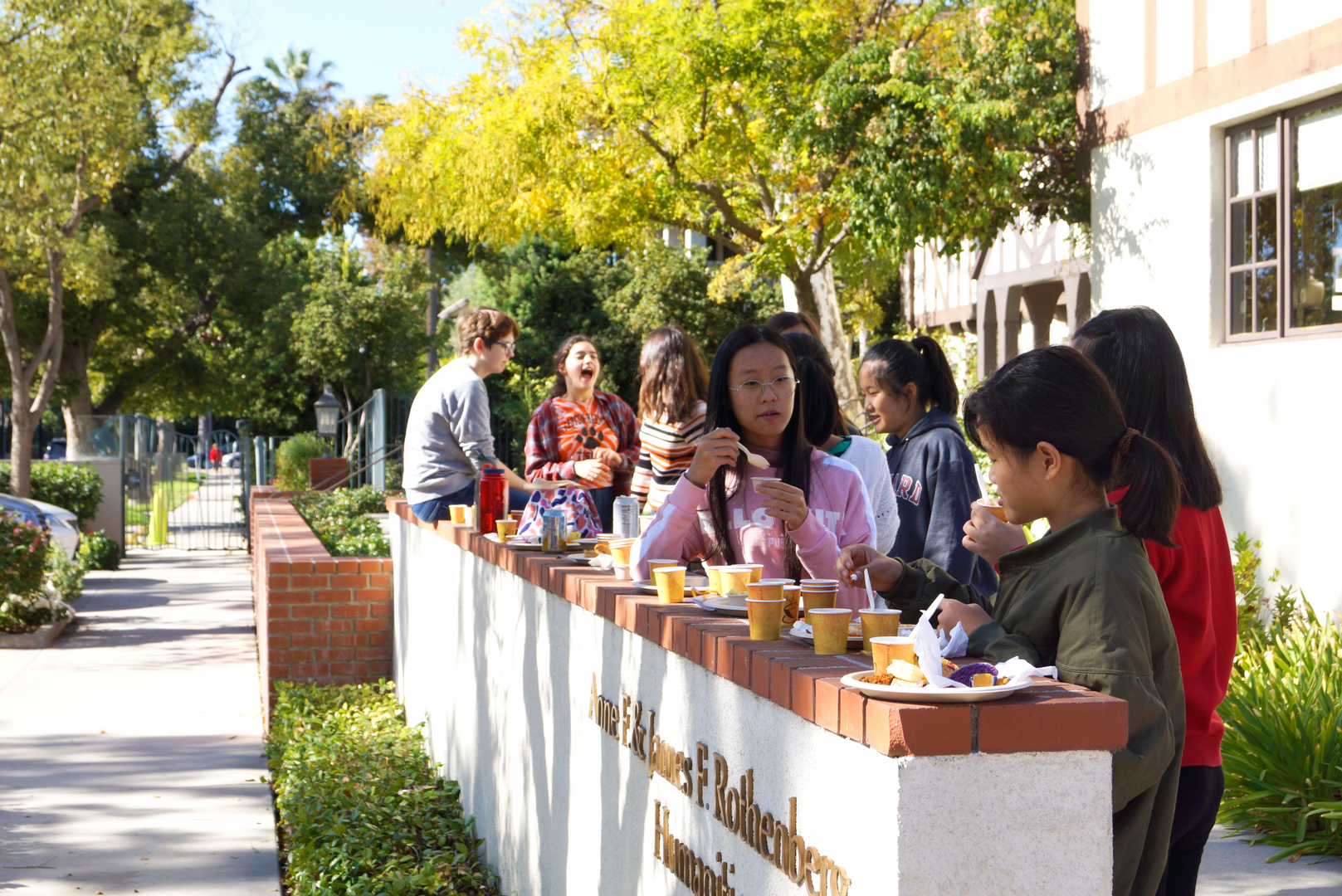 Students gather in front of the Humanities Center to enjoy their meals