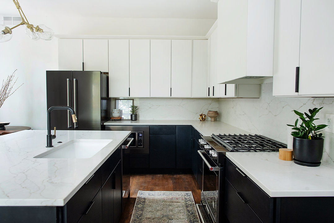 modern black and white kitchen with black faucet and hardware pulls with modern gold light fixture