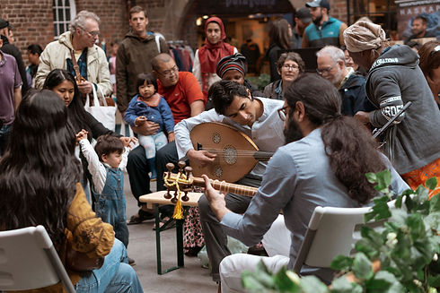 Musicians are seated in a circle playing music while market goers watch.