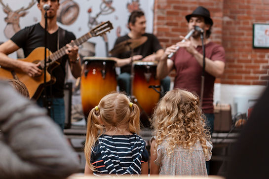 Two young kids with blonde hair are facing away from the camera watching musicians play instruments.