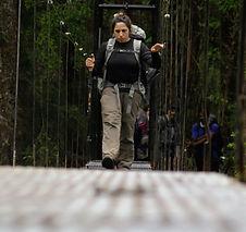 Una estudiante cruza un puente colgante durante una expedición en Patagonia.