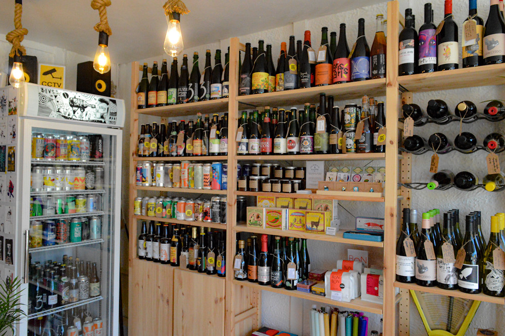 Shelves of wine and beer next to a fridge full fo beer.