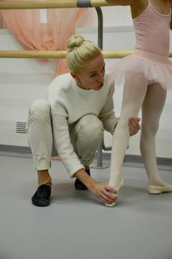 Педагог поправляет юную балерину