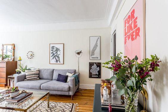 Salón con un sofá gris de 2 plazas, una mesa central acristalada y posters en las paredes