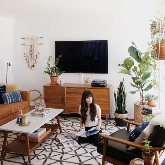 Salón con muebles mid-century, alfombra étnica y grandes plantas de interior