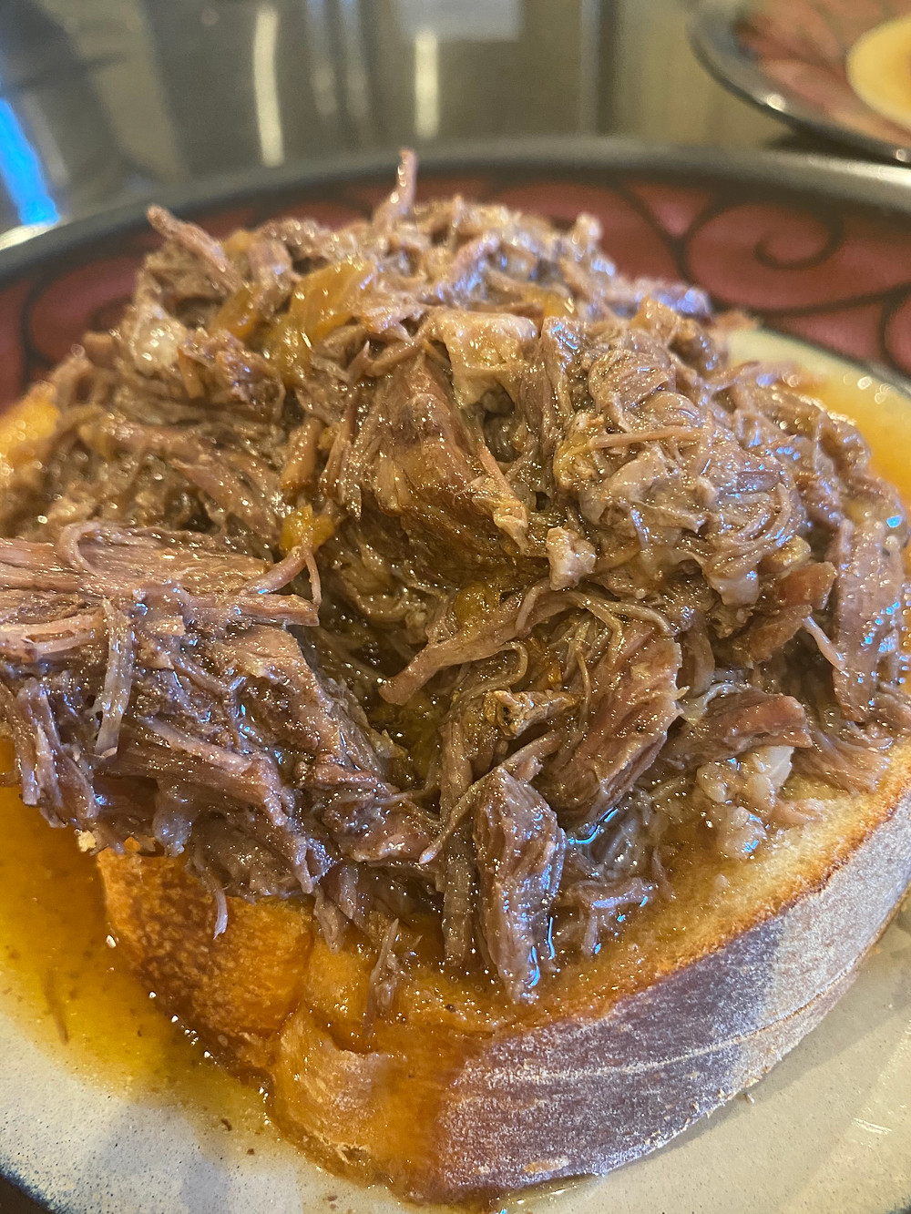 A beautiful pile of moist beef sitting atop a slice of homemade white bread dripping with au jus.