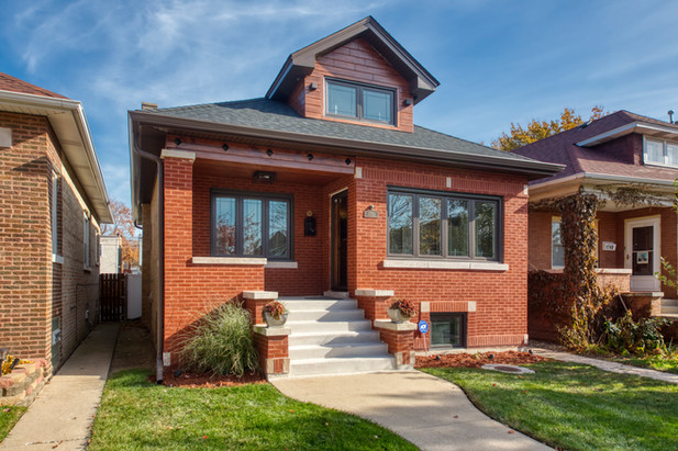 AB significantly improved the curb appeal of his Austin bungalow by addressing every part of the home's exterior—roof, windows, tuckpointing, concrete steps, and lighting. Plus, the torched cedar siding on the dormer adds unique flare.