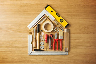 Conceptual house composed of DIY and construction tools on hardwood flooring, top view.jpg
