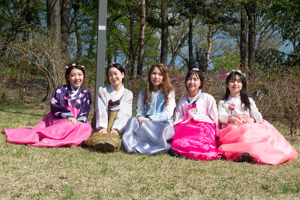 Tradition and modernity - girls in traditional costumes at the imperial palace in Seoul