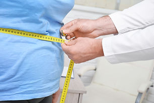 Male doctor measuring waist of overweigh