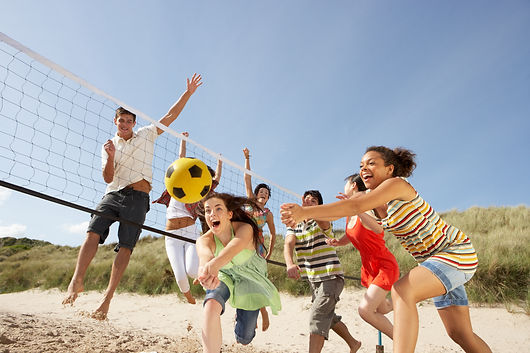 Group Of Teenage Friends Playing Volleyb