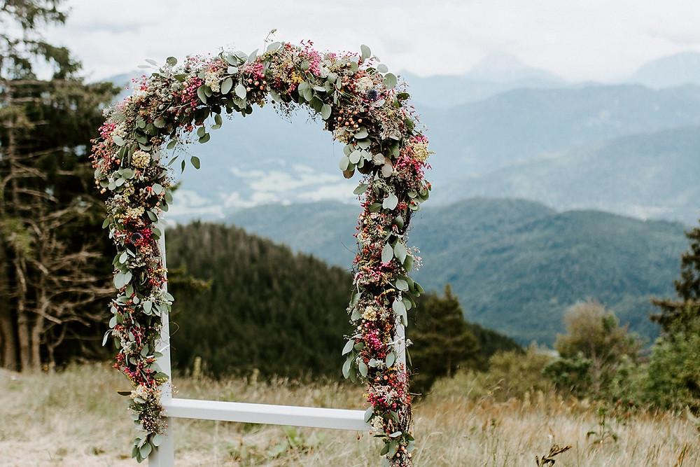 Traubogen aus bunten Blumen und im Hintergrund das Bergpanorama
