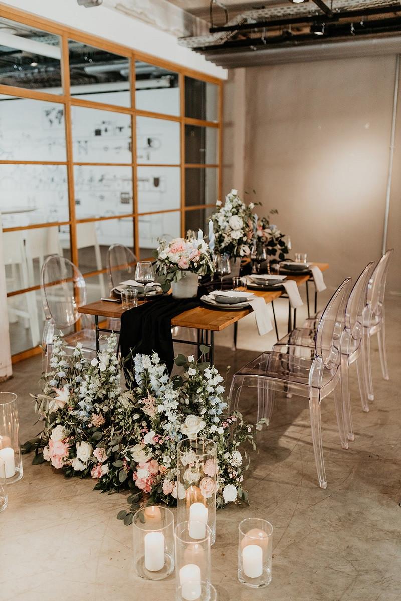 Hochzeitstafel im Industrialstiel mit Floristik in den Farben blau, rosa und schwarz