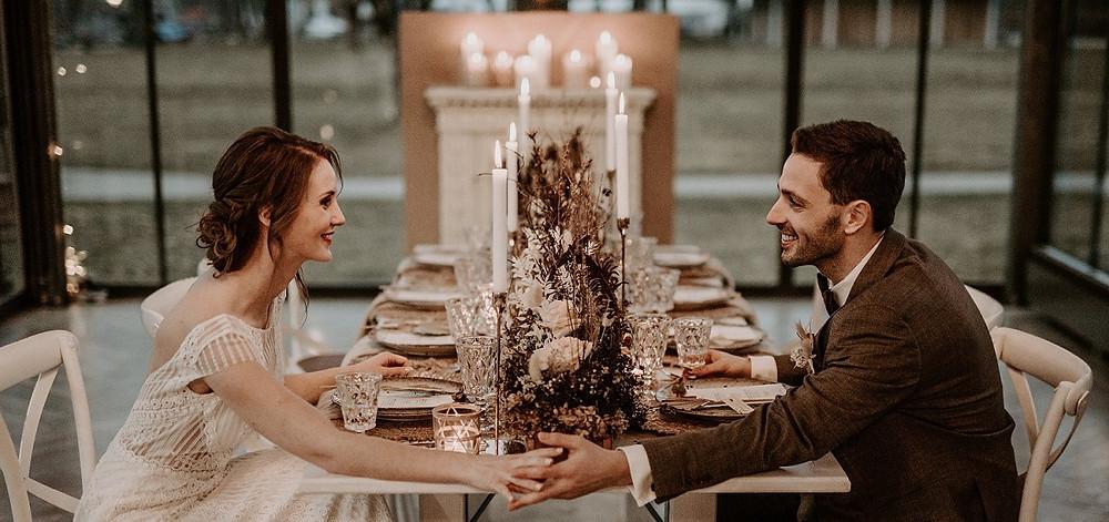 Hochzeitspaar das sich in die Augen schaut und auf einer Tiny Wedding sitzt