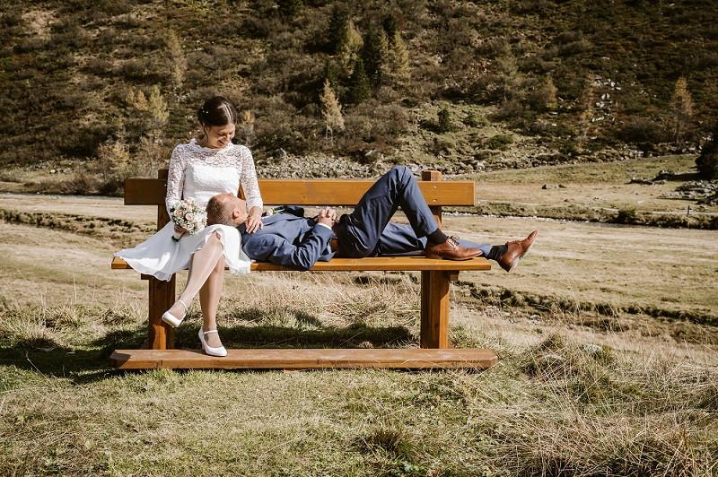 Brautpaar sitzt auf Bank in den Bergen