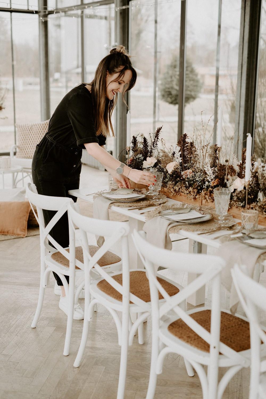 Hochzeitsplanerin dekoriert den Tisch für eine Boho Hochzeit