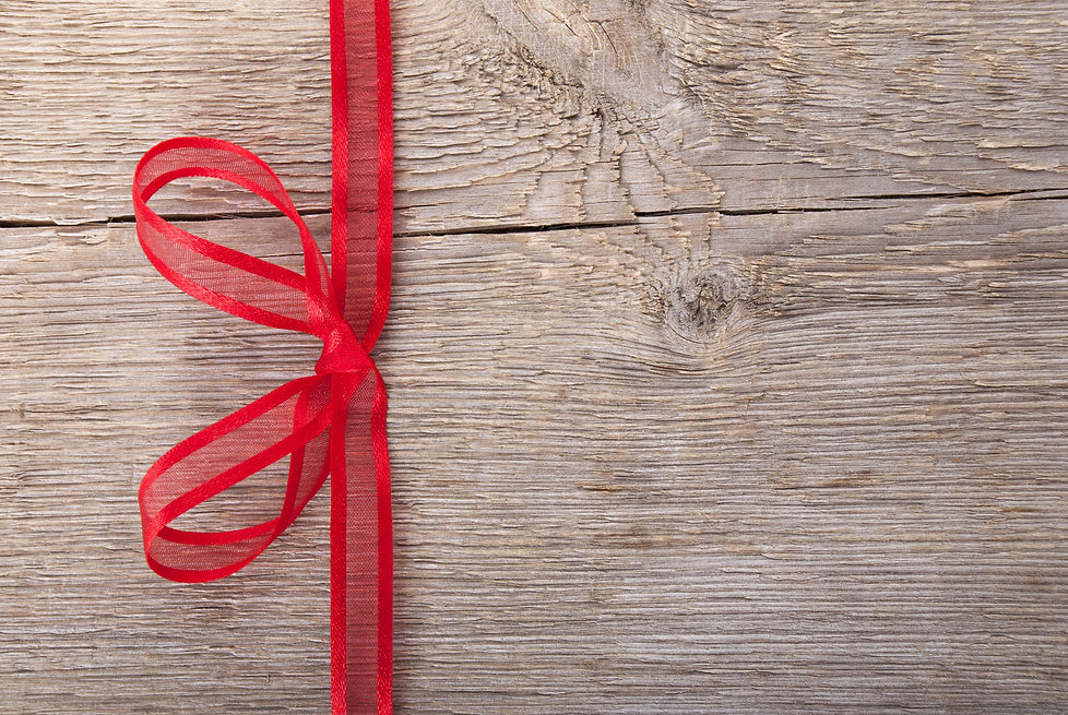 a red bow on a wooden background with co