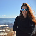 A woman wearing sunglasses stands in front of a large body of water.