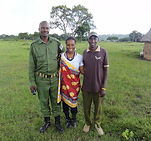 A woman stands with two Maasai men in a grassy field.