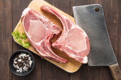 Raw Pork Chop Steak On Cutting Board And Cleaver On Wooden Background.
