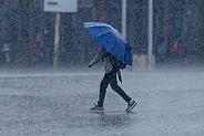 1200px-A_man_walks_through_heavy_rain_un