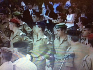 Shimon Deri, with his back to the screen  in the right side corner, black beret, walking past the Honor Guard