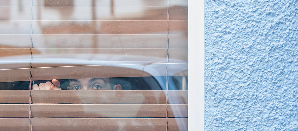 Person peeps trough closed window blinds, using his finger to lift one of the blinds