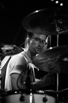 Black and white gig photograph of InMe drummer looking at camera at Bristol Exchange