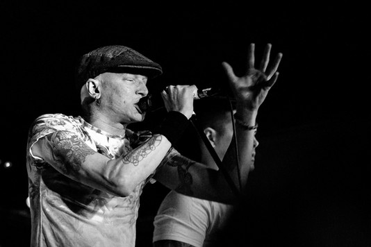 Black and white gig photograph of InMe front-man with microphone and hand in air at Bristol Exchange