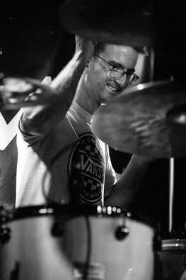 Black and white gig photograph of InMe drummer smiling at Bristol Exchange
