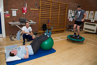 Physiotherapist with patients in gym