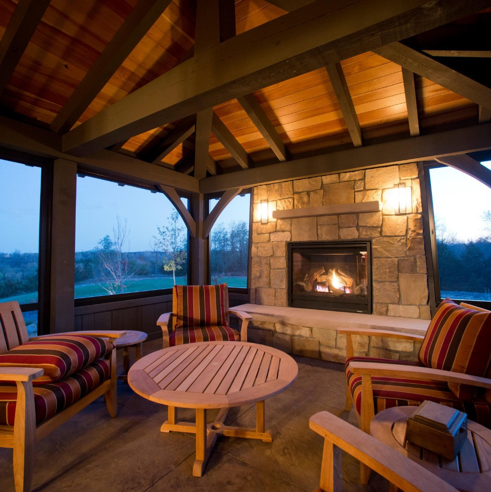 Custom Timber Frame Home in Hanover MN Built by Renaissance Builders Inc © A timber frame 3 season porch with a stone fireplace and stamped concrete patio. White pine post and beams support a beautiful wood ceiling. The screen panels offer breathtaking views of the surrounding countryside