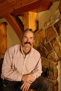 A photo of Phil Bjork from Great Northern Woodworks standing in front of a wood burning fireplace in a timber frame home