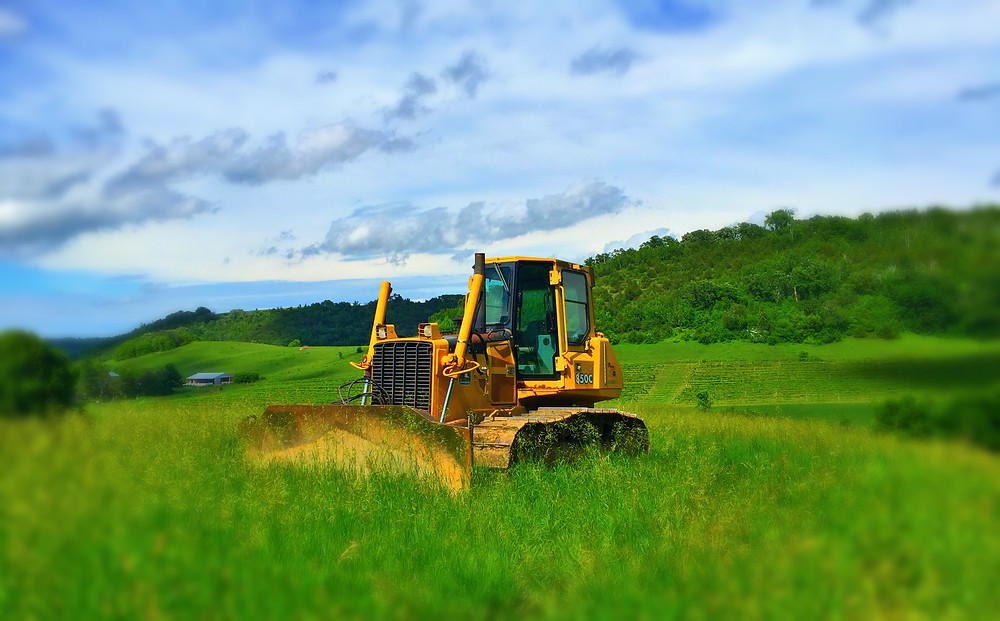 A yellow bulldozer perched up on top of a bluff in a grassy field