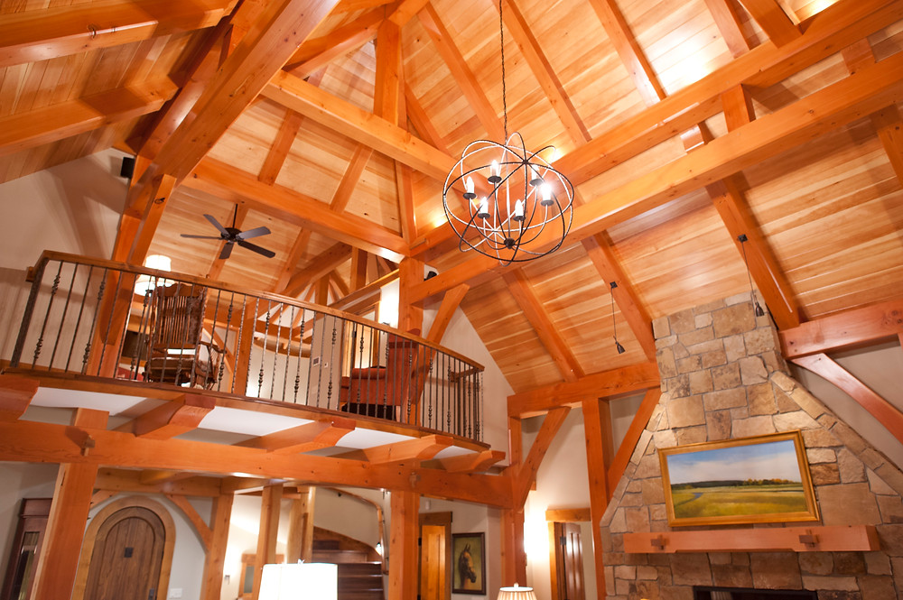 The interior of a timber frame cottage in Hanover, MN. It shows douglas fir posts and beams with pine ceiling boards and a curved staircase. The front entry door is made of walnut and the upper level loft doubles as a guest bedroom