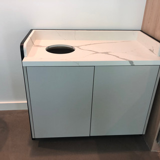 Floating trash cabinet on a steel frame with stone top