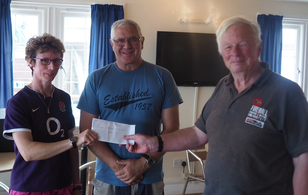 Sharon of Regatta and Carnival Committee, accepts donation from Dave Beer, LRSC
