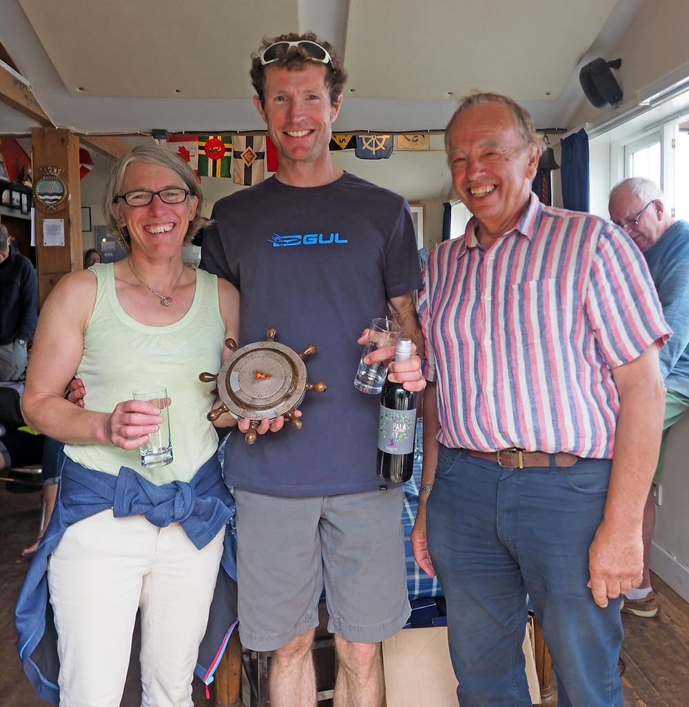 Tony Fastnedge, right, presents Championship,of the Day Regatta Wheel to winners Luke and Emma McEwan